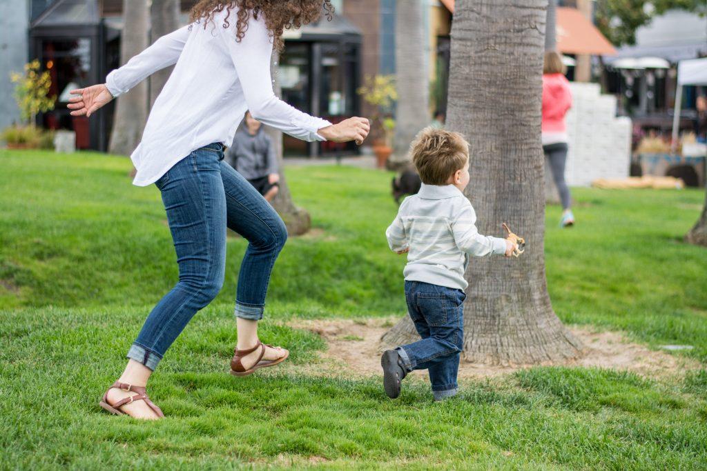 Dr. Jolene Brighten chasing her son in a park.